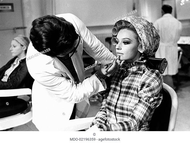 Make-up artist of the TV programme Canzonissima Enzo Amato taking care of the lips of dancer and presenter Raffaella Carrà before the TV show begins