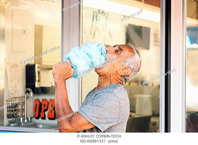 Senior man eating cotton candy, Long Beach, California, USA