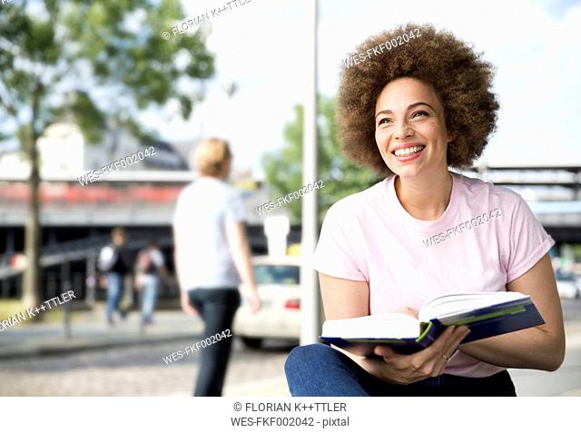 Young woman reading book, outdoor
