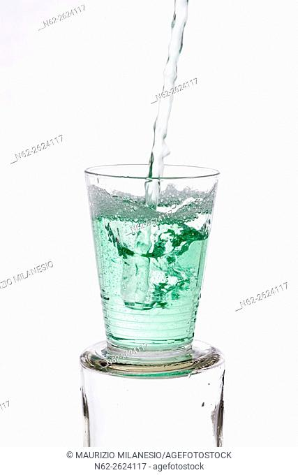 Green drinks poured into a glass, on a white background
