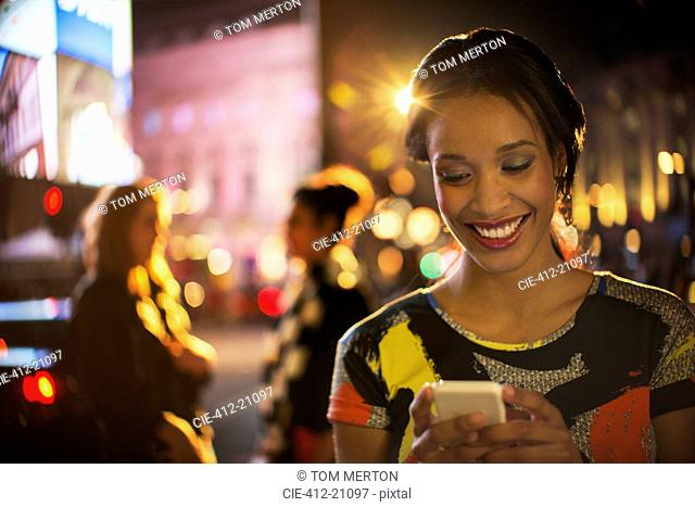 Woman using cell phone on city street at night