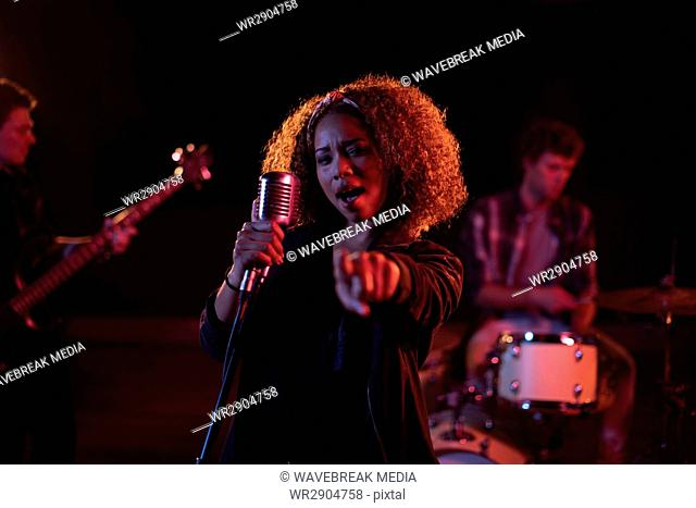 Portrait of woman singing on microphone
