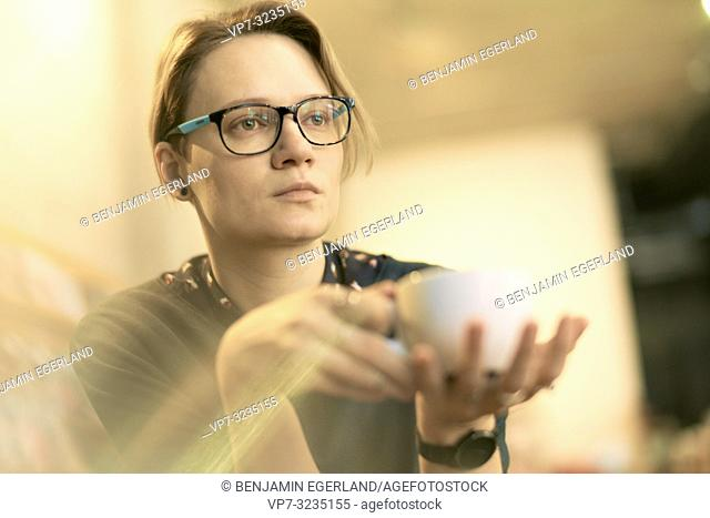 woman with coffee cup, indoors, wearing spectacles, in Munich, Germany