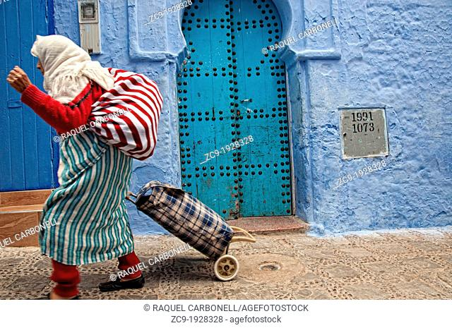 Woman walking by the streets of the blue medina Chefchaouen, Rif region, Morocco