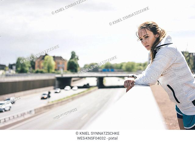 Sportive young woman leaning on railing at motorway
