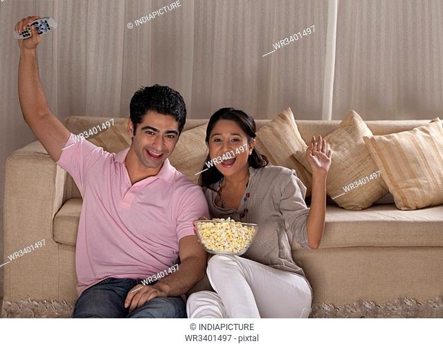 Happy young couple enjoying while watching TV at home