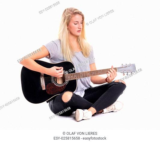 young girl sitting cross-legged and playing guitar