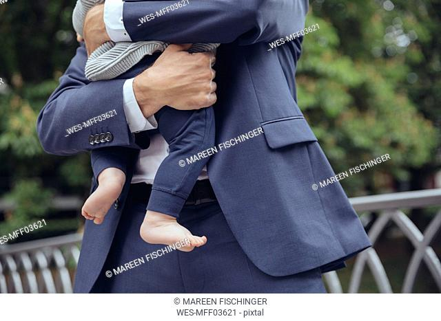 Businessman clutching baby boy outdoors