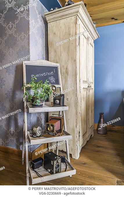 Old wooden tray stand with displayed antique film cameras next to tall wooden armoire in living room inside an old 1839 Canadiana cottage style home