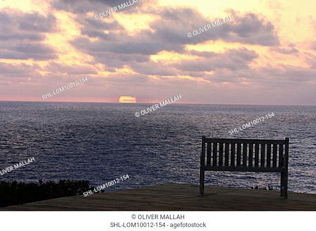 Wooden bench on patio overlooking sunset on the ocean