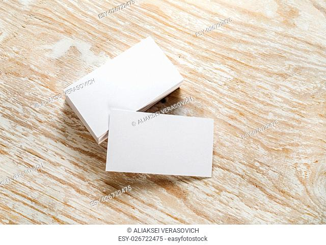 Blank business cards with soft shadows on light wooden background. Template for design presentations and portfolios. Studio shot