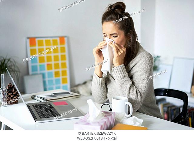 Ill woman at home at desk blowing her nose