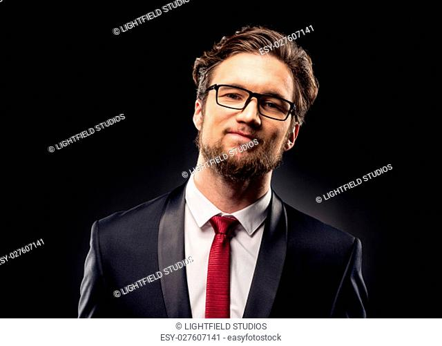 Bearded businessman in eyeglasses smiling at camera on black