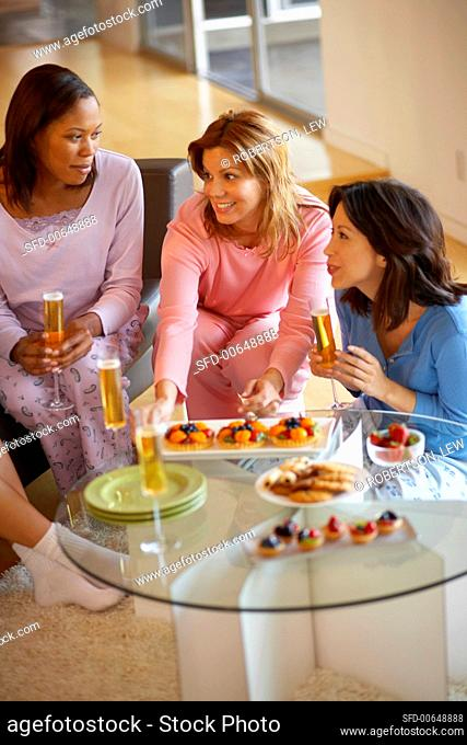Women chatting with sparkling wine and fruit tarts