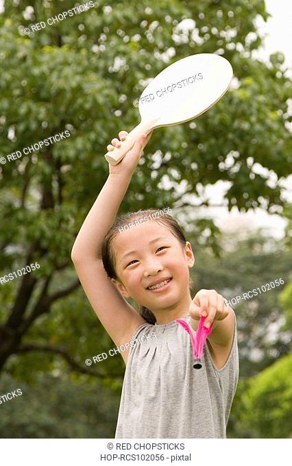 Girl holding a racket and a shuttlecock in a garden