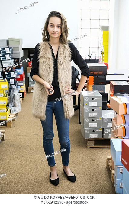 Tilburg, Netherlands. Attractive Polish female immigrant working in a safety shoe shop, servicing Polish immigrant workers