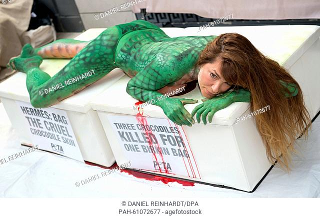 Actress Alexandra Kamp wearing crocodile-like body paint lies in front of a store of French apparels manufacturer Hermes during a campaign of animal rights...