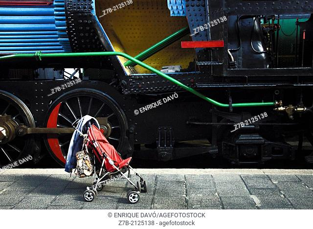 A baby carriage close to a old train in the station of the train museum of Madrid, Spain