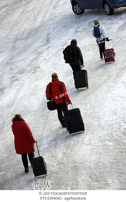 people pulling wheeled luggage walk across ice at kirkenes harbour finnmark norway europe