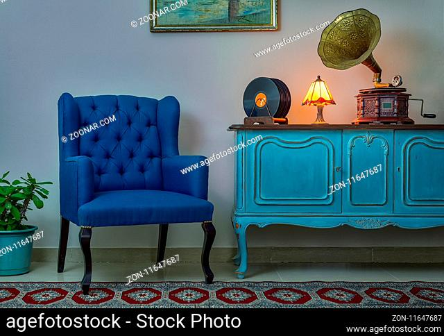 Interior shot of blue armchair, vintage wooden light blue sideboard, lighted antique table lamp, old phonograph (gramophone)