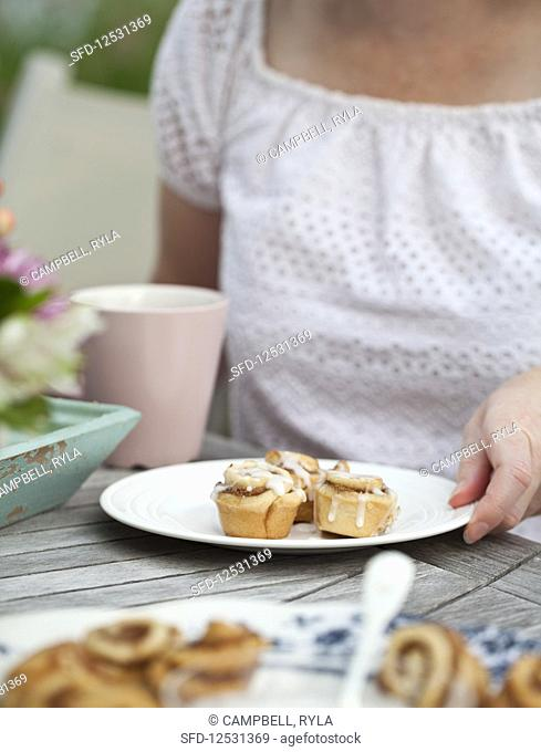 A woman sitting at an outdoor brunch with a coffee cup, plate of cinnamon buns and flowers
