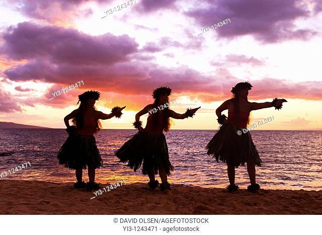 Three hula dancers at sunset at Palauea, Maui, Hawaii