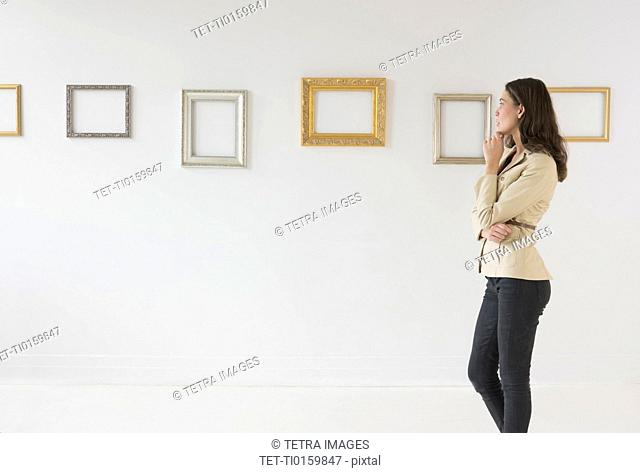 Woman looking at blank pictures in art gallery