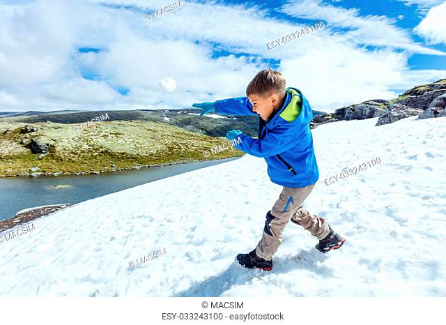 Best Norway hike. Cute boy playing snow in the summer mountains