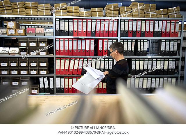 11 December 2018, Hessen, Bad Arolsen: Christian Groh, head of the Archive Department, leafs through a file in front of a file cabinet in the provisional...