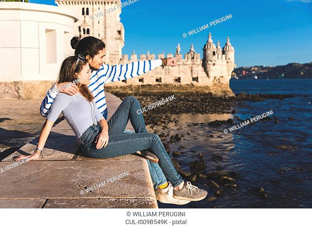 Young couple sitting on wall by sea, Belem Tower in background, looking at view
