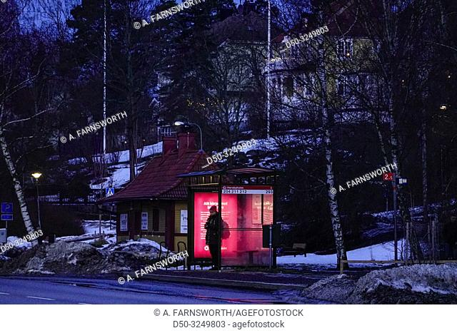 Stockholm, Sweden. Commuters at a bus stop on the island of Lidingö