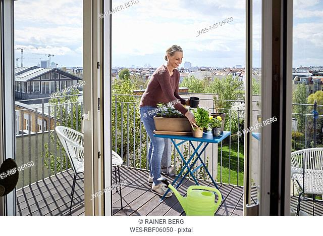 Smiling mature woman caring for plants on balcony
