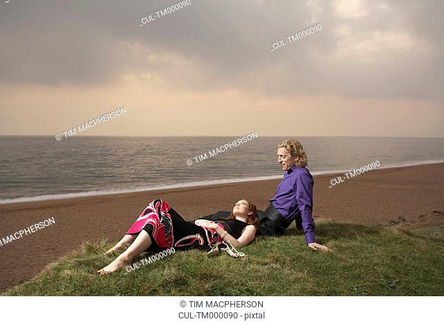 Couple sitting next to a beach