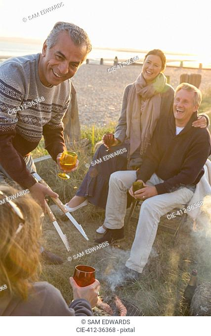 Smiling mature couples drinking wine and barbecuing on sunset beach