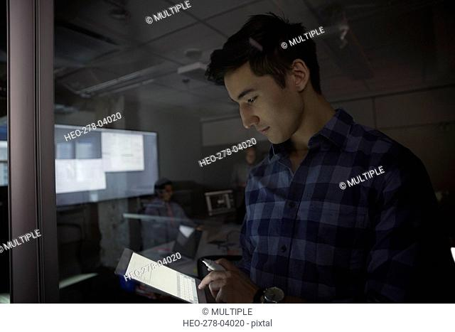 Businessman using digital tablet dark conference room meeting