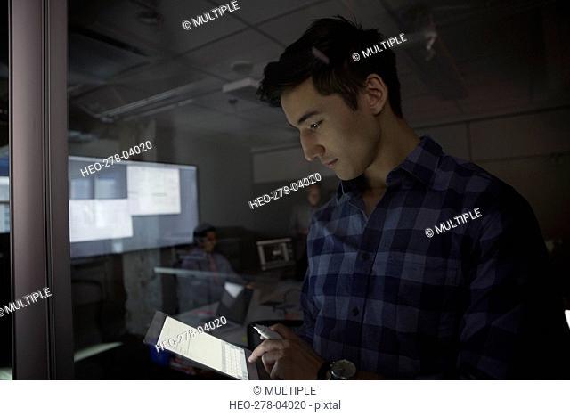 Businessman using digital tablet dark conference room meeting
