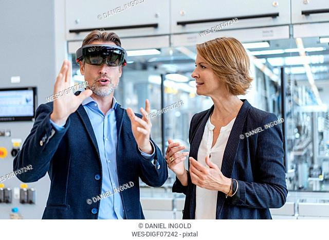 Businessman with AR glasses and businesswoman in a modern factory