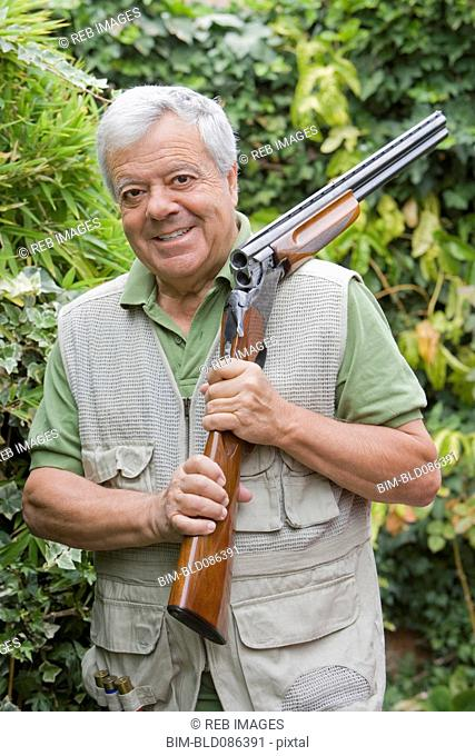 Senior Chilean man holding shotgun