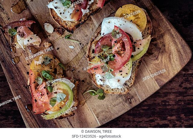 Sourdough bruschetta with heritage heirloom tomatoes, mozarrella, baby basil, cracked black pepper and olive oil