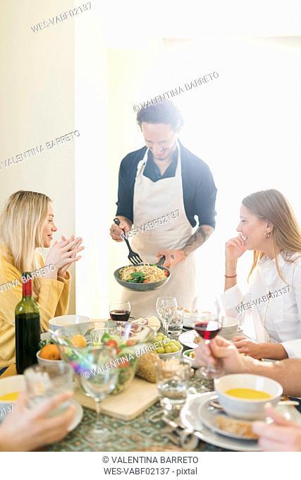 Friends having lunch together, host serving pasta