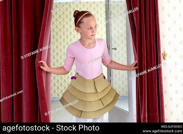 Girl wearing cardboard tutu looking around