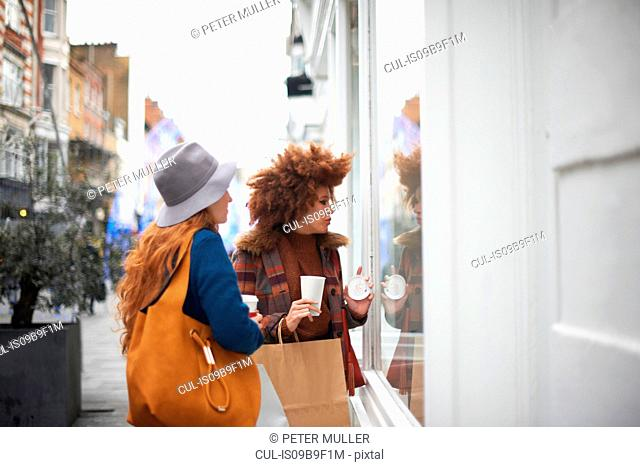 Two young women looking in shop window