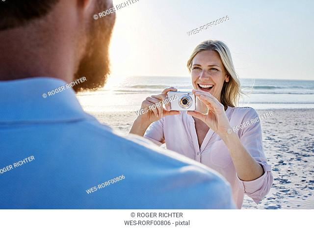 Happy woman taking a picture of man on the beach