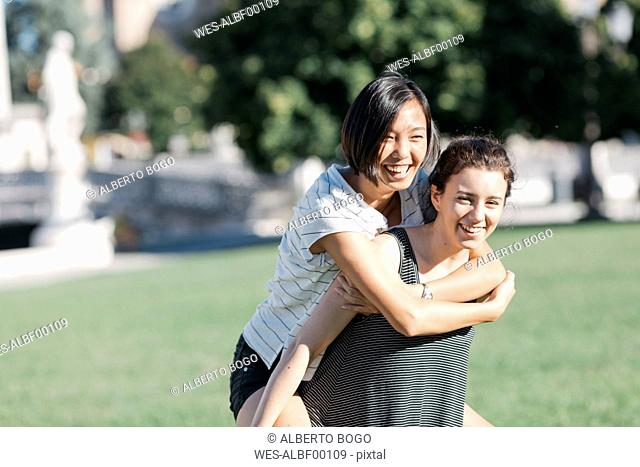 Young woman giving her friend a piggyback ride in the park