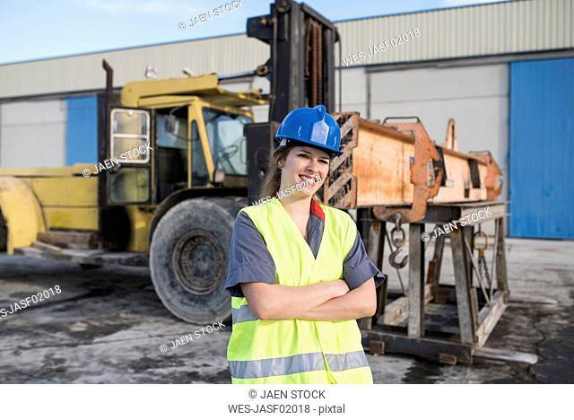 Portrait of confident female worker on industrial site near bulldozer