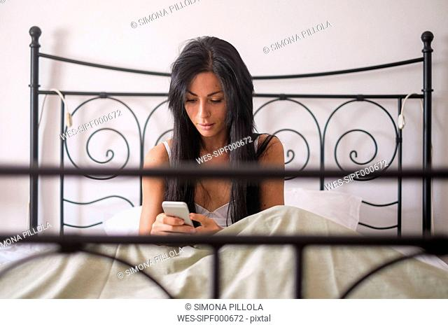Woman sitting in bed, smartphone