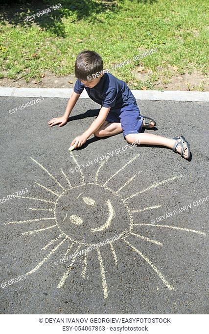 Child drawing sun on asphalt in a park