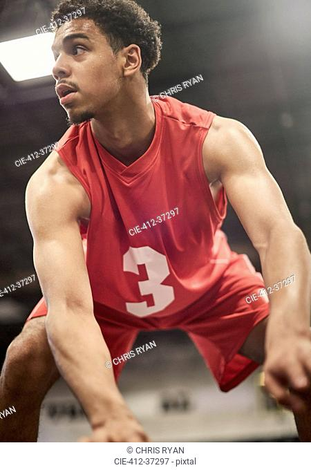 Determined young male basketball player dribbling the ball