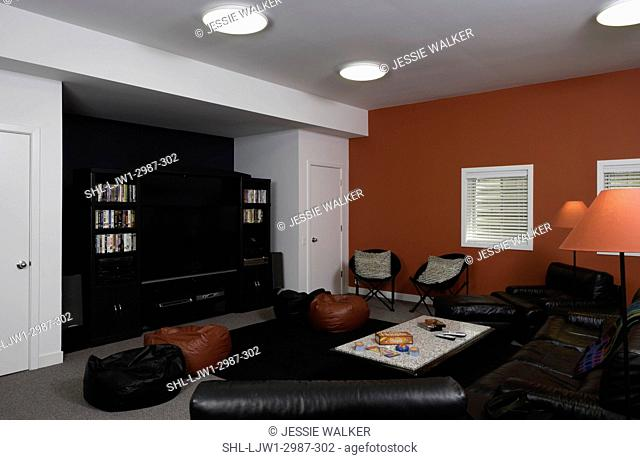 BASEMENT : red, black and white color blocked walls, big screen tv, bean bags and leather sofa and chairs, coffee table with games