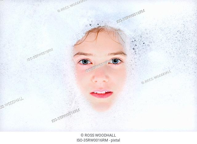 Close up of girl floating in bubble bath